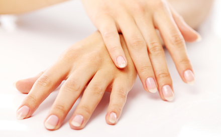 Beautiful hands with french manicure against white background